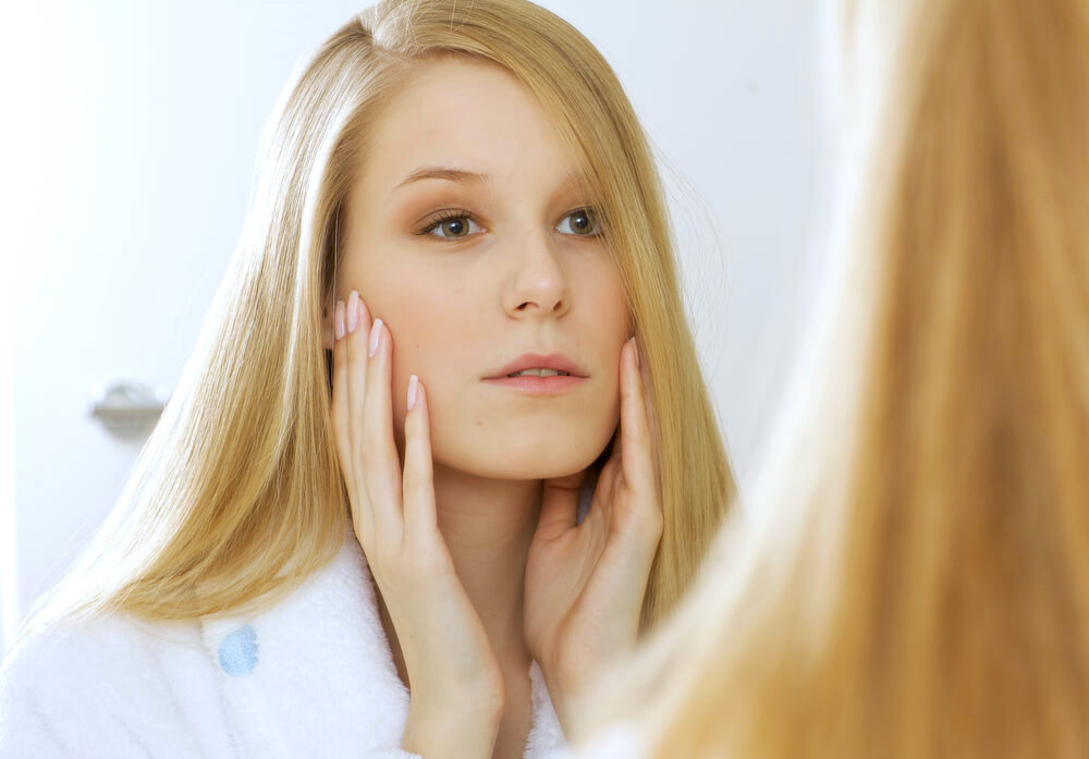Young blonde woman checking skin in mirror