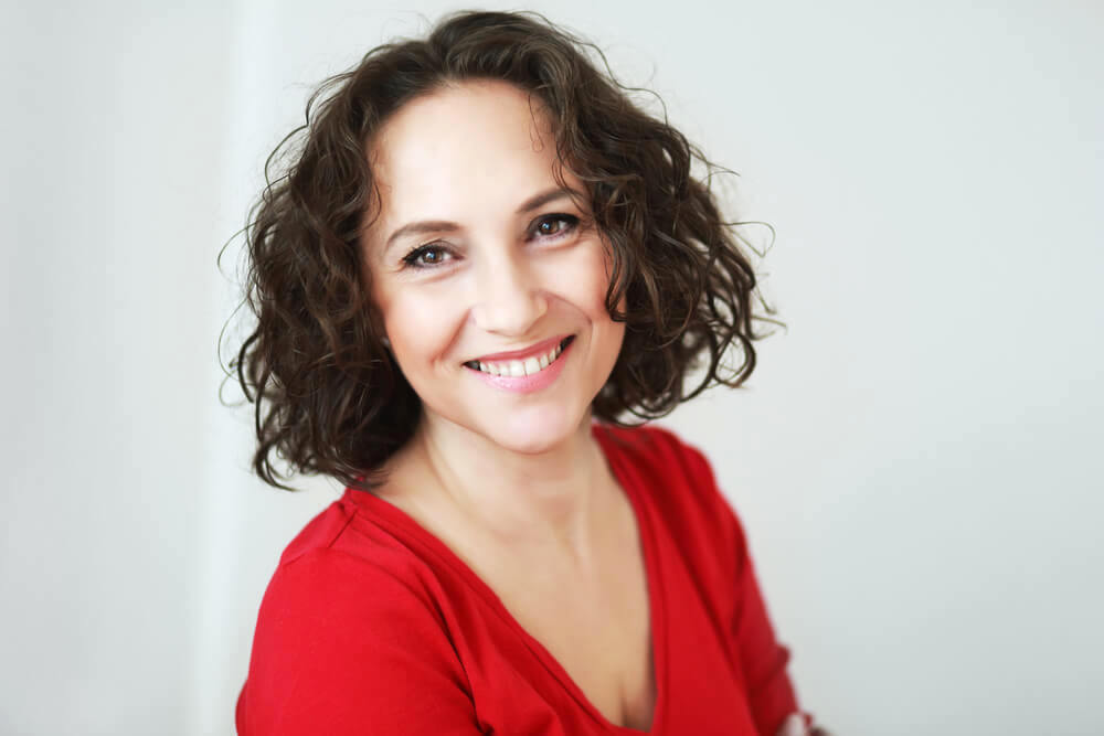 Happy smiling middle-age woman with short wavy hair