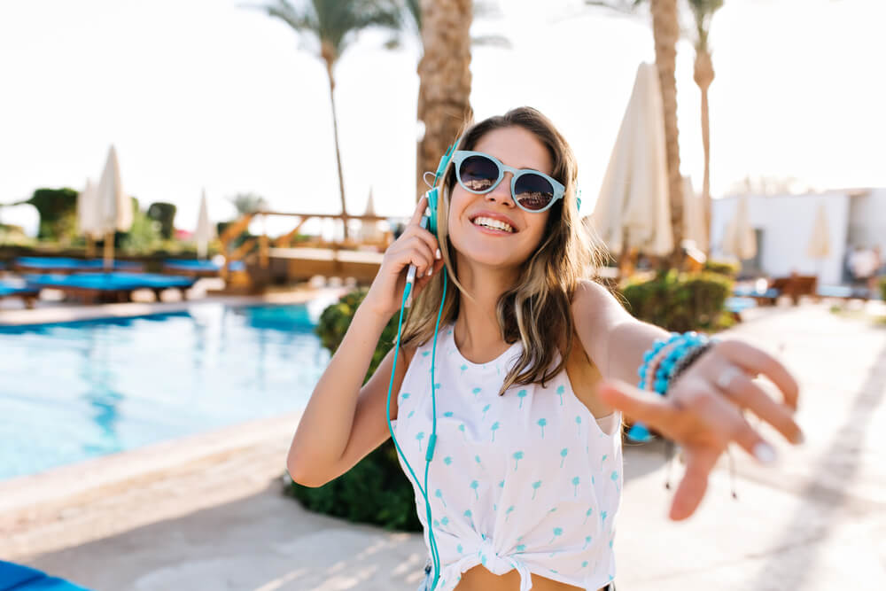 Happy young woman listening to music on her earphones
