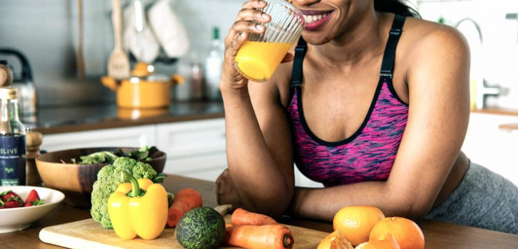 Athletic woman enjoying a glass of orange juice in the kitchen