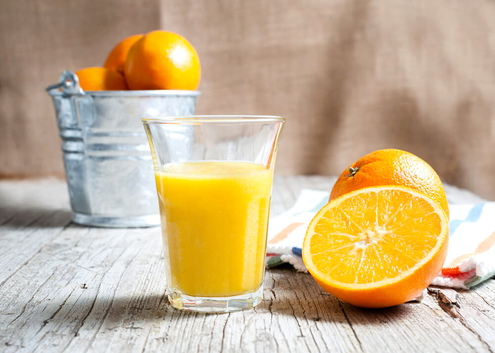 A glass of fresh orange juice, with halved orange