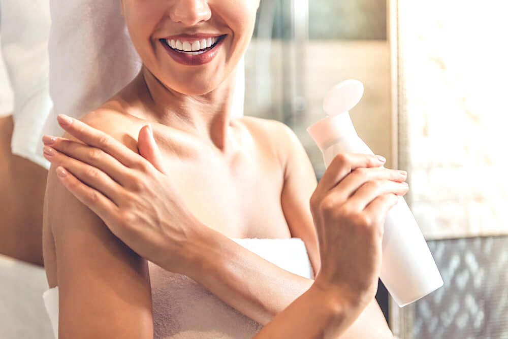 Woman applying moisturizer on shoulder