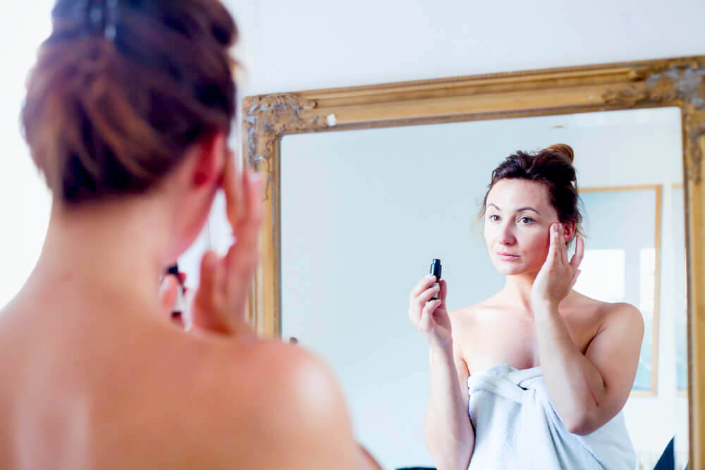 Woman applying eye cream in front of mirror