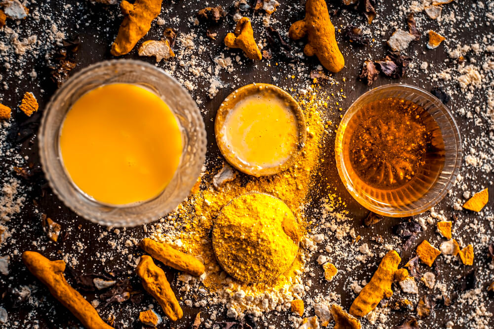 Turmeric paste in small clay bowls surrounded by turmeric powder