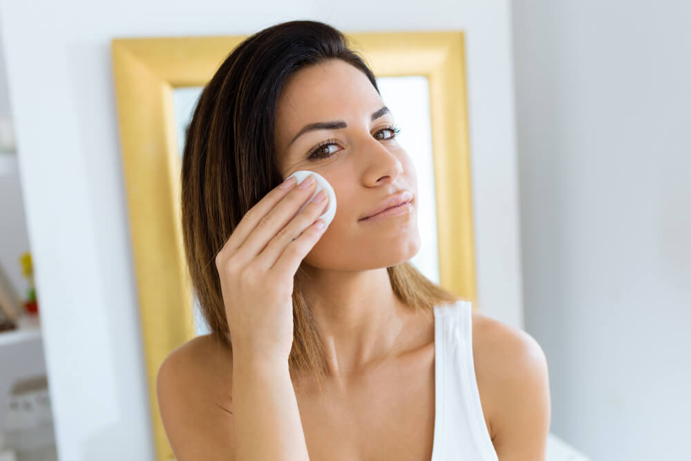 Woman applying skincare with cotton pad
