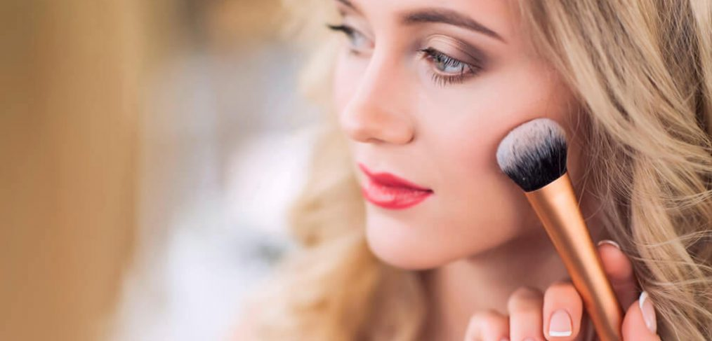 Makeup artist applying blush on beautiful woman's cheek