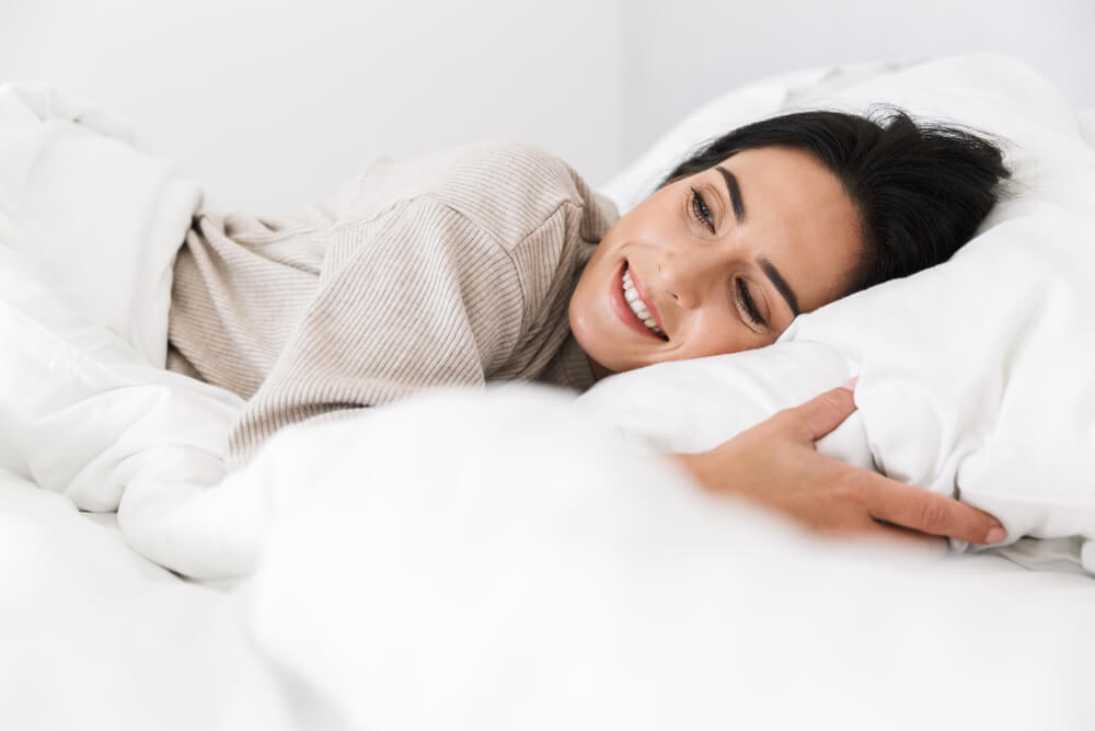 Happy woman smiling and sleeping in bed