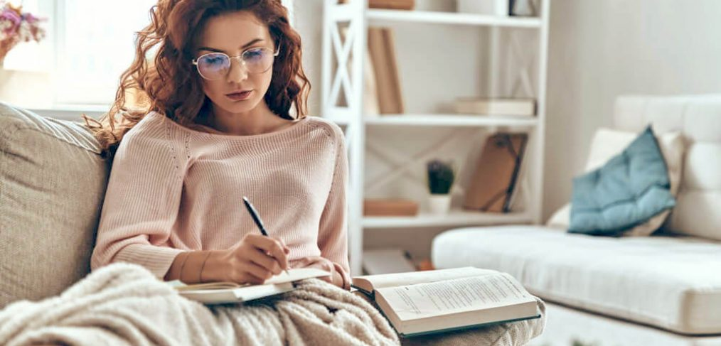 Focused woman writing in journal, on sofa at home