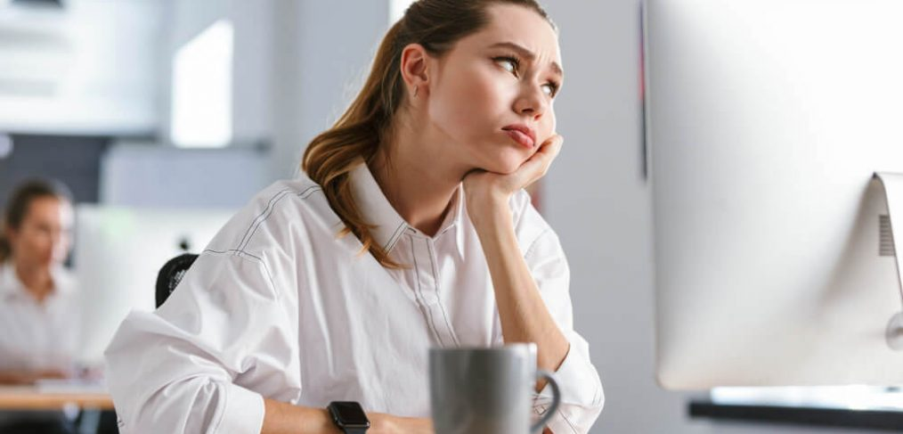Woman looking stressed and bored at work