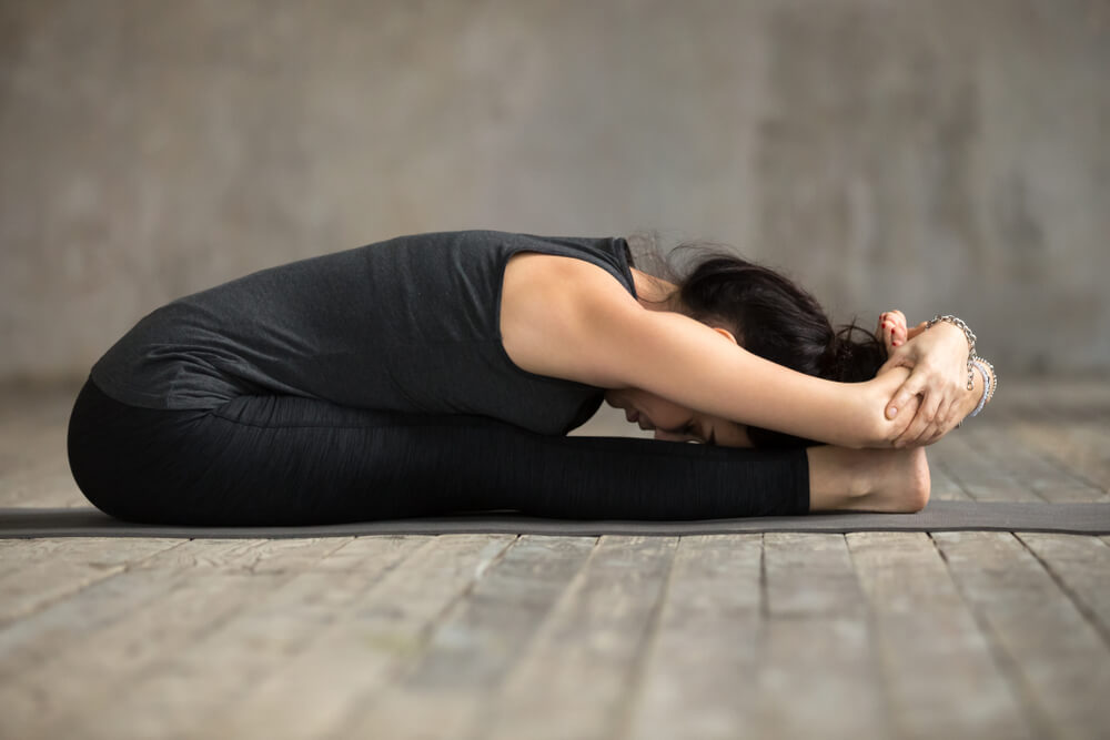 Woman in seated forward fold pose